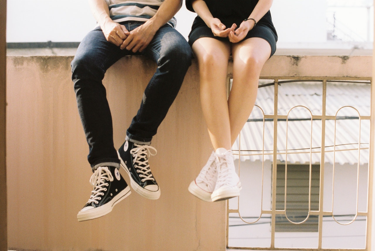 The legs of an unmarried couple who are sitting on a wall relaxing